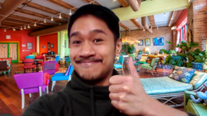 Bryan gives a thumbs-up, using a colorful virtual zoom background from Catalyst Ranch.